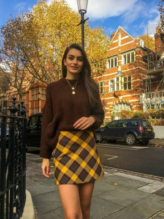 Girl in a yellow plaid miniskirt, brown sweater; ideas to wear a mini skirt with a sweater in autumn-winter