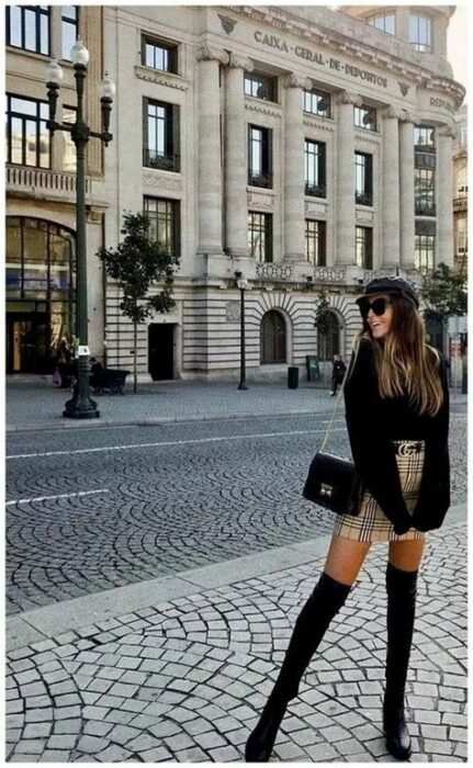 Girl wearing a black miniskirt with a black wide-sleeved sweater; ideas to wear a mini skirt with a sweater in autumn-winter