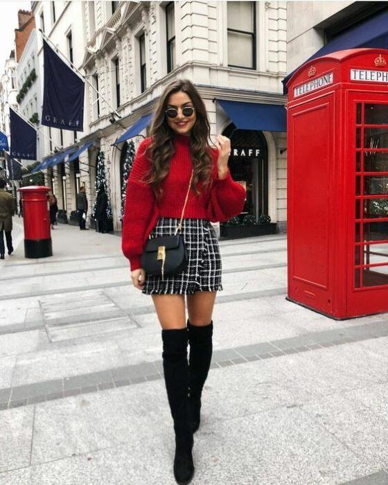 Chica usando minifalda a cuadros y suéter rojo; ideas para usar minifalda con suéter en otoño-invierno