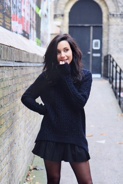 Girl in a black miniskirt and oversize sweater; ideas to wear a mini skirt with a sweater in autumn-winter