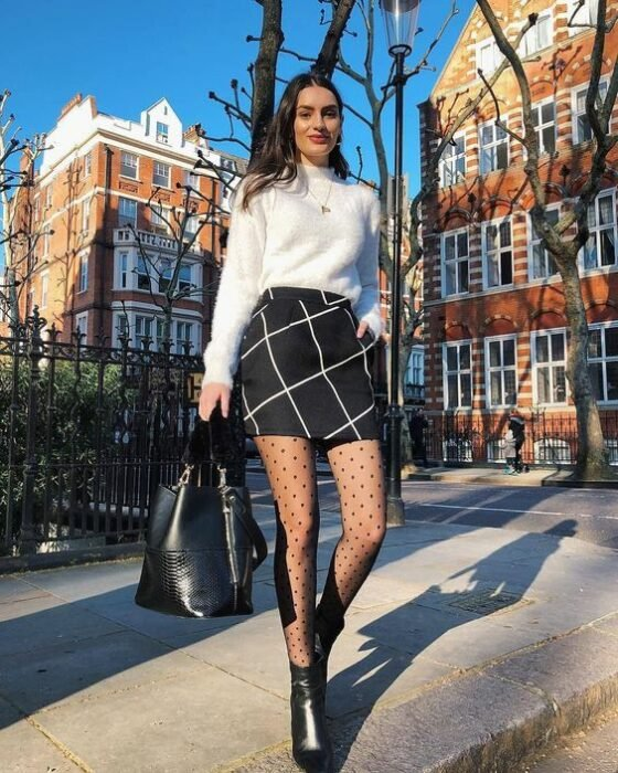 Girl wearing plaid miniskirt with white sweater and stockings; ideas to wear a mini skirt with a sweater in autumn-winter