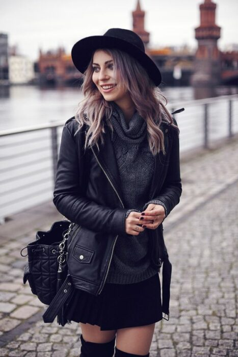 Girl in a black miniskirt, leather jacket; ideas to wear a mini skirt with a sweater in autumn-winter