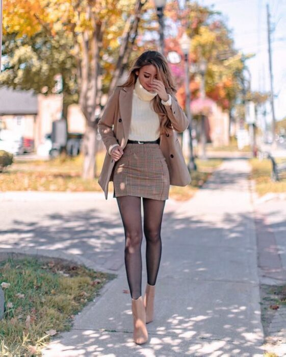 Girl with matching miniskirt and raincoat; ideas to wear a mini skirt with a sweater in autumn-winter