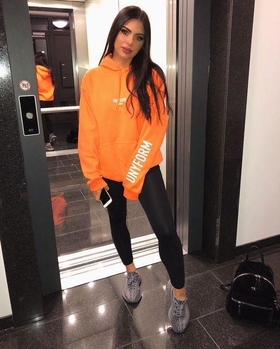 Chica llevando conjunto deportivo con sudadera en color naranja; Ideas para usar color naranja en tu outfit