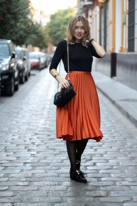Chica llevando falda plisada en tono naranja metálico con medias en negro; Ideas para usar color naranja en tu outfit