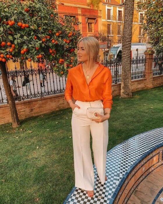 Chica usando una blusa de satín en color naranja con pantalón sastreIdeas para usar color naranja en tu outfit