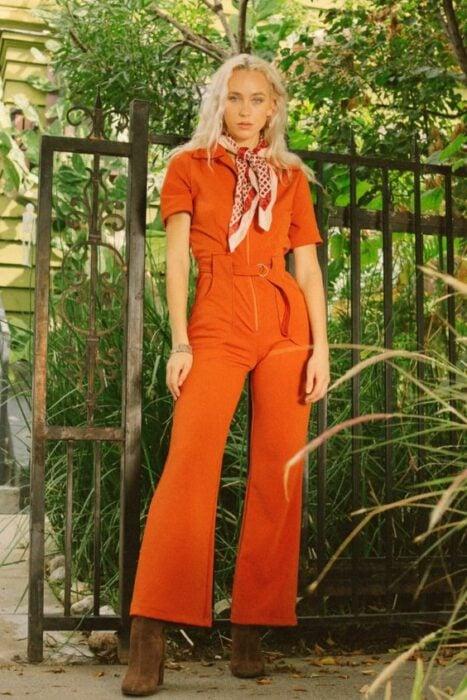 Chica llevando jumpsuit en tono naranja con hebillas metálicas; Ideas para usar color naranja en tu outfit