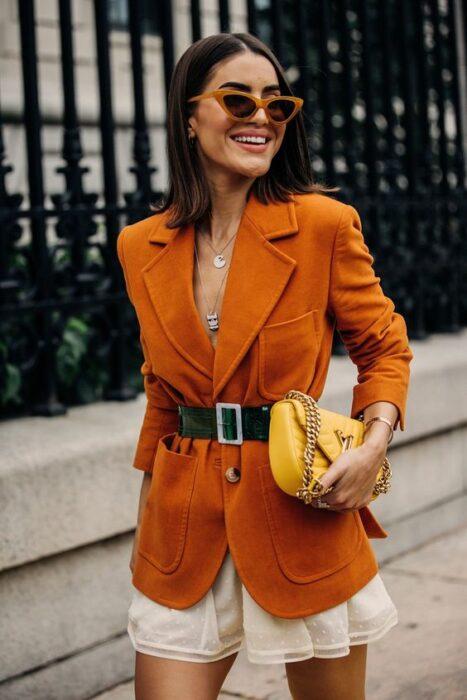 Chica llevando blazer en tono naranja con accesorios amarillos en contrasteIdeas para usar color naranja en tu outfit