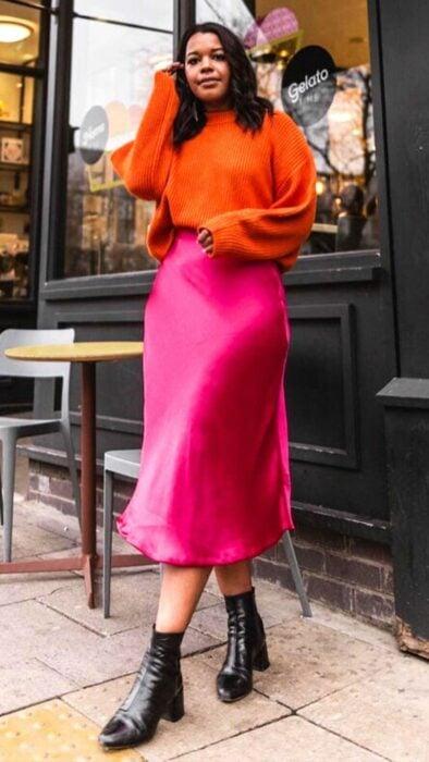 Chica llevando suéter naranja con falda de satín rosa fuscia; Ideas para usar color naranja en tu outfit