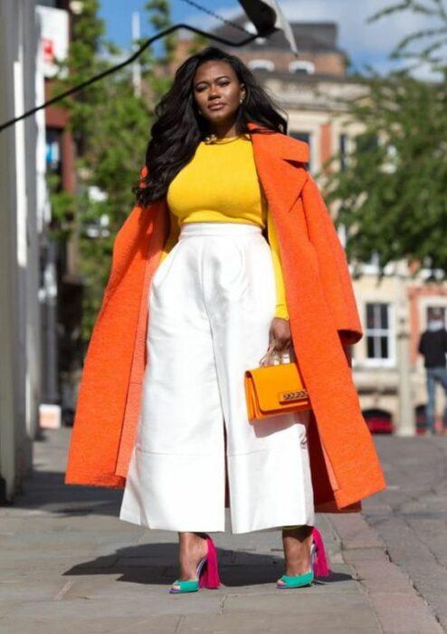 Chica llevando pantalón blanco con gabardina en naranja; Ideas para usar color naranja en tu outfit