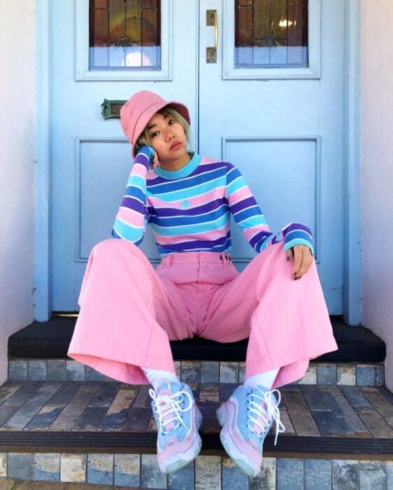 Looks coloridos aesthetic; mujer coreana de cabello corto y rubio sentada en las escaleras frente a una puerta azul, con ropa de colores, gorro pescador rosa, suéter rayado morado, azul fuerte y claro, pantalón acampanado y tenis chunky en tonos pastel