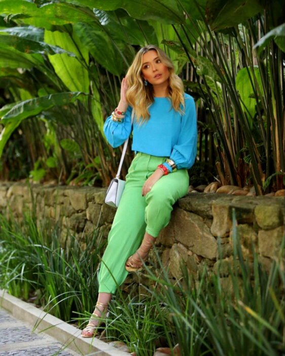 Colorful aesthetic looks; woman sitting on stone fence with plants, blonde, medium hair, hairstyle with loose waves, colorful outfit, sky blue puff-sleeved blouse, green dress pants, white handbag, red and gold bracelets, high-heeled sandals