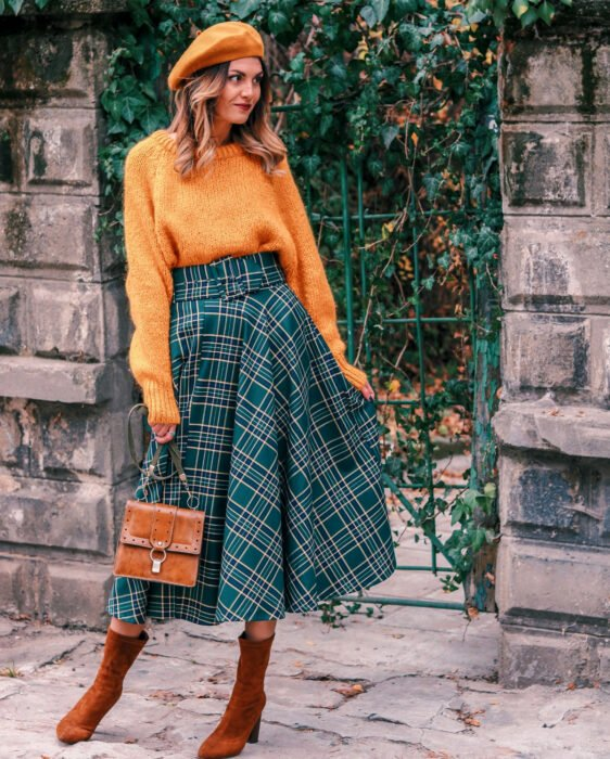 Colorful aesthetic looks; smiling woman in colorful outfit, French beret and orange knitted oversized sweater, long green plaid skirt, small brown handbag, suede ankle boots and high heels, ombré hair brown at the roots faded to blonde at the tips