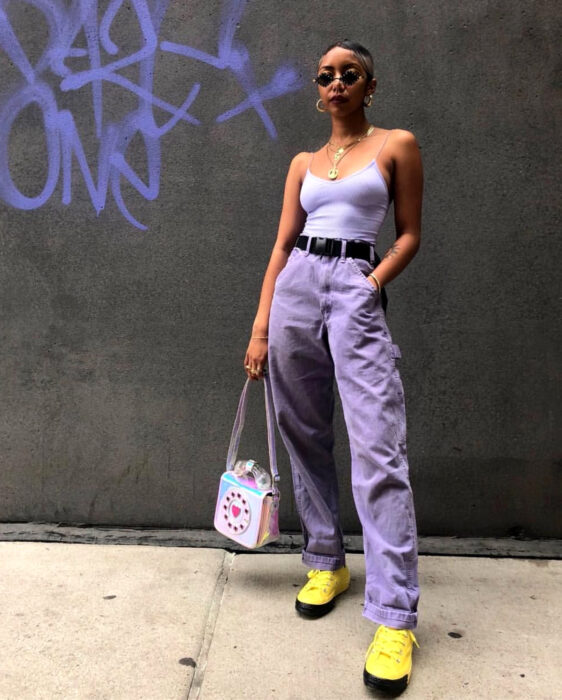 Colorful aesthetic looks; African American woman with brown skin, short hair, small sunglasses, lilac tank top, mom jeans, purple jeans, yellow tennis shoes with black, belt, clutch bag in the shape of an old telephone in holographic colors