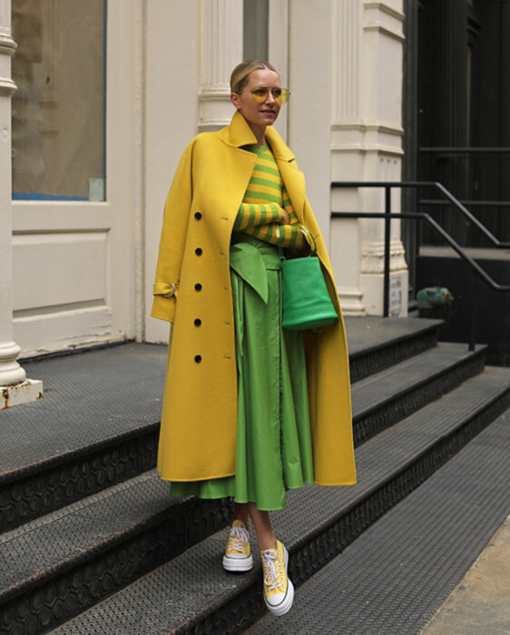 Colorful aesthetic looks; woman taking pictures on stairs and in front of white door, blonde hair in a low ponytail, yellow sunglasses, long jacket, trench coat, long-sleeved blouse with yellow and green stripes, modern skirt, converse tennis shoes, handbag