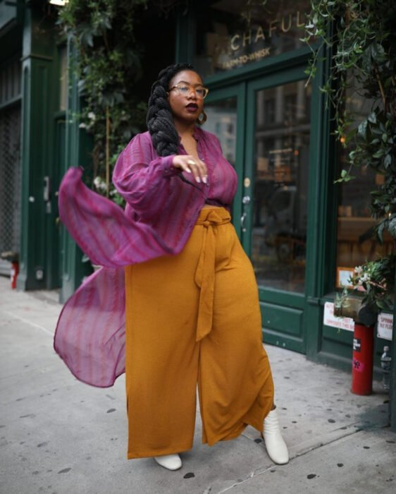 Colorful aesthetic looks; African American woman, brunette, with black hair combed in a thick braid, retro magnifying glasses, wine red lipstick, pink chiffon blouse with vertical stripes, light mustard yellow pants, white ankle boots