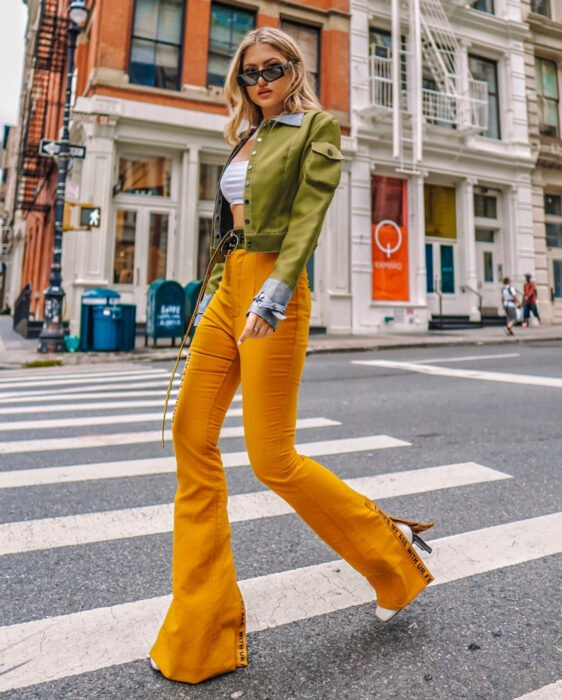 Colorful aesthetic looks; woman walking on the street in pedestrian crossing, blonde, medium hair, wavy, loose and disheveled, rectangular sunglasses, white crop top, army green jacket, orange yellow flared jeans, white ankle boots