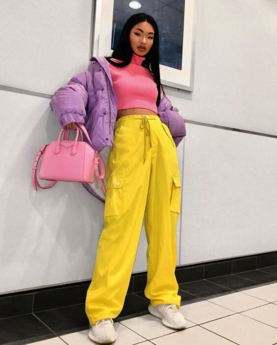 Colorful aesthetic looks; woman with slanted eyes, long, straight black hair leaning against the wall, loose, colorful outfit, pink crop top, large purple jacket, yellow baggy pants, white tennis shoes, handbag