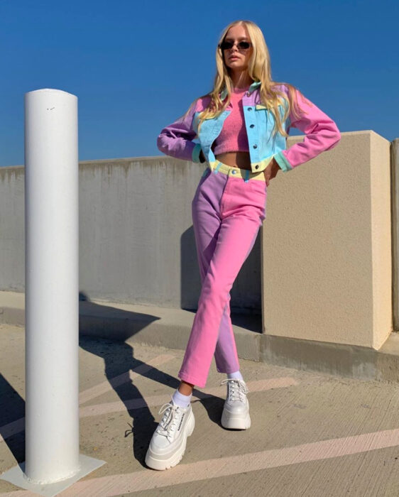 Colorful aesthetic looks; blonde woman standing in parking lot with colorful outfit, blonde hair, straight, long and loose, pink crop top, jeans, denim pants in pastel, lilac, yellow and blue tones, matching jacket, chunky sneakers with chunky sole and platform white color, square sunglasses