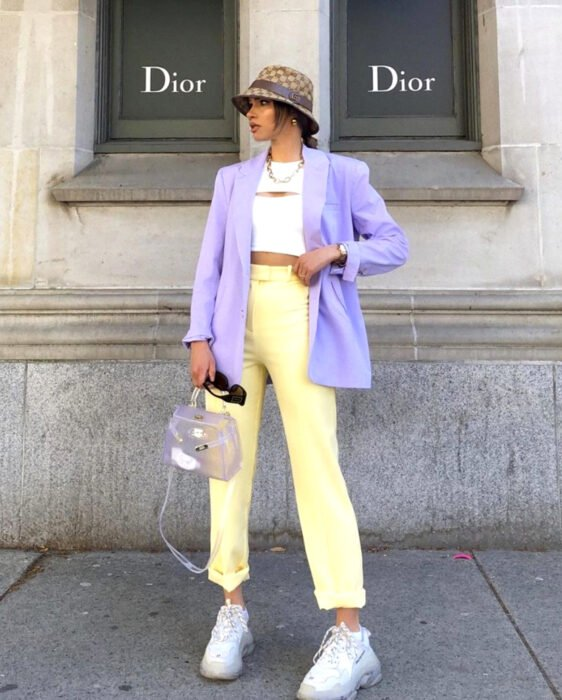 Colorful aesthetic looks; Woman with combed brown hair, with brown plaid fisherman's hat, white dress crop top, pastel yellow pants, blazer, lilac purple jacket, transparent handbag, square sunglasses, large white chunky tennis shoes, in front of Dior store