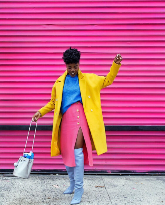 Colorful aesthetic looks; African American woman with dark skin, Chinese hair, smiling, dressed in colorful outfit, blue blouse, pink pencil skirt with leg slit, long gray knee-high boots, yellow coat blazer, handbag and long earrings