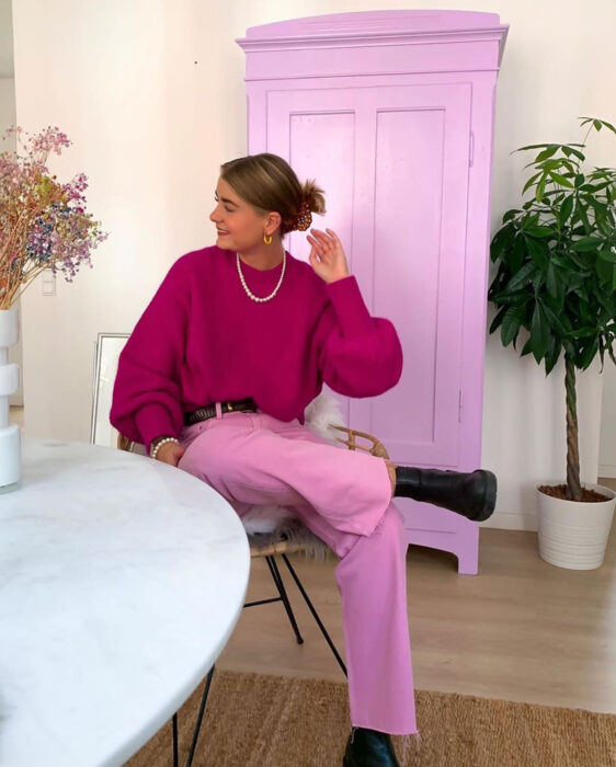 Colorful aesthetic looks; smiling woman sitting in the living room in front of a baby pink wardrobe, blond brown hair clipped back, pink sweater and pants, white pearl necklace, brown belt and black ankle boots