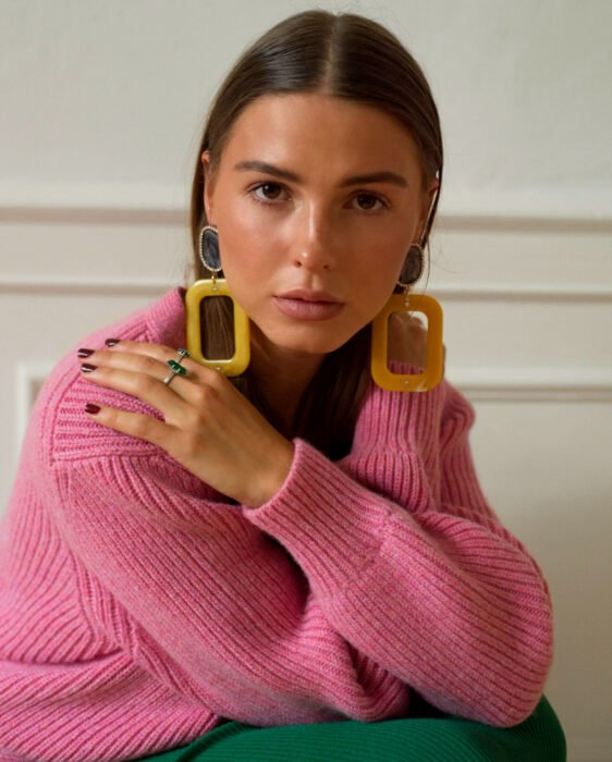 Colorful aesthetic looks; brown-eyed woman with hands on shoulders and serious expression, straight, loose brown hair, retro-style yellow rectangular earrings, pink knitted sweater, green skirt and rings, nails with wine-red polish