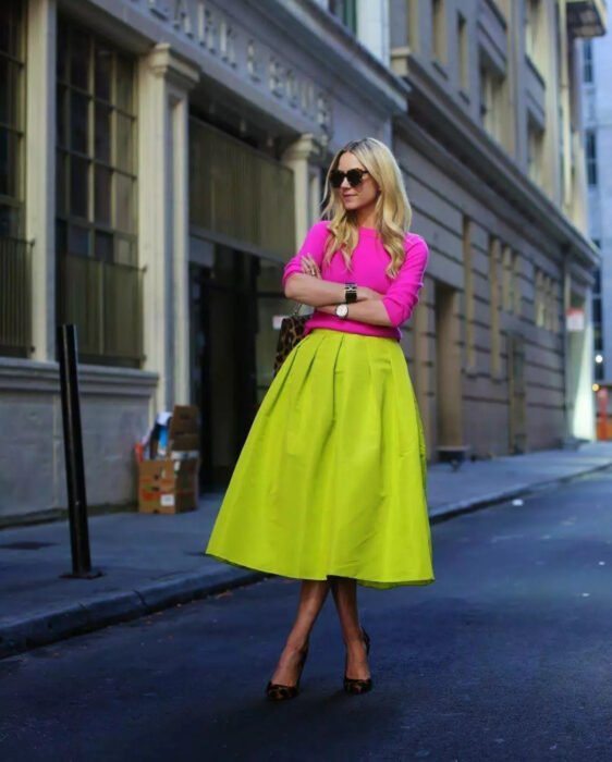 Colorful aesthetic looks; girl posing in the street, long blonde hair, loose and wavy hairstyle, large, rectangular dark sunglasses, Mexican pink 3/4 sleeve sweater, neon green A-line long skirt, animal print sneakers, women's watch, bracelet, handbag