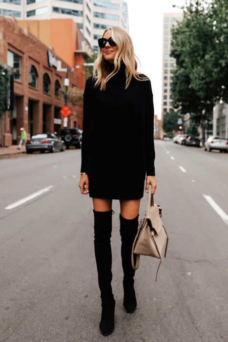 Girl wearing a long black dress and high boots