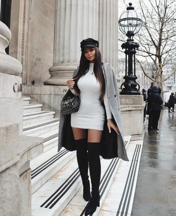 Girl wearing a white dress with high boots and gray coat