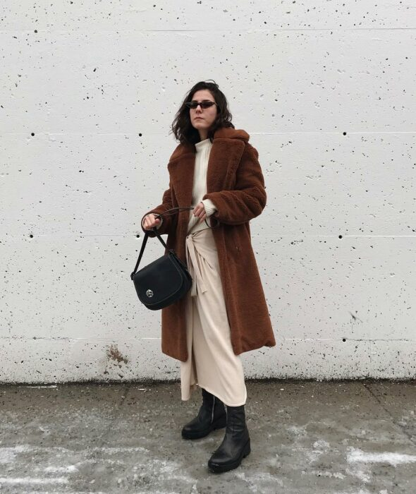 Girl wearing a brown dress with a long coat, booties and black handbag