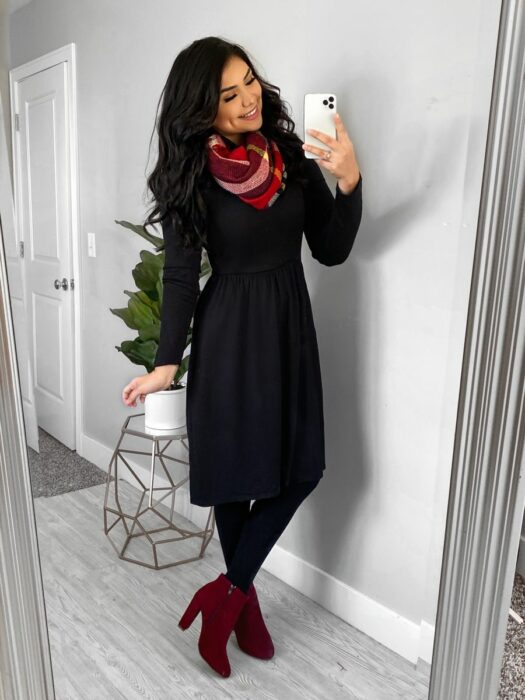 Girl wearing a long black dress with a scarf and red ankle boots