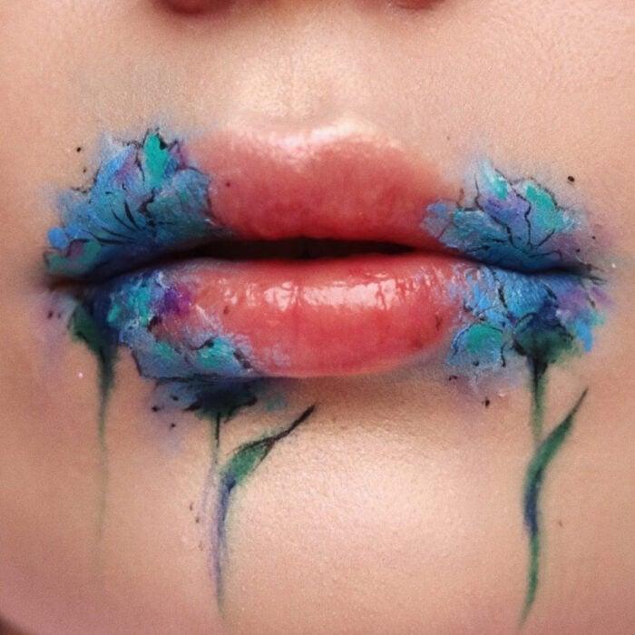 Maquillaje artístico de labios por maquilladora Tatiana Rose; boca con labial color carne y dibujos de flores azules en las orillas