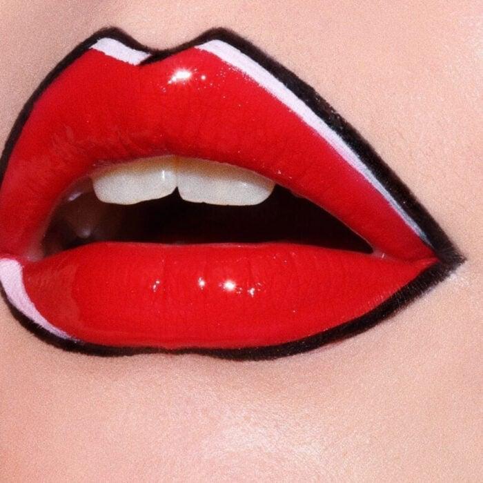 Maquillaje artístico de labios por maquilladora Tatiana Rose; boca con labial rojo con efecto de cómic con contorno negro y blanco, gloss