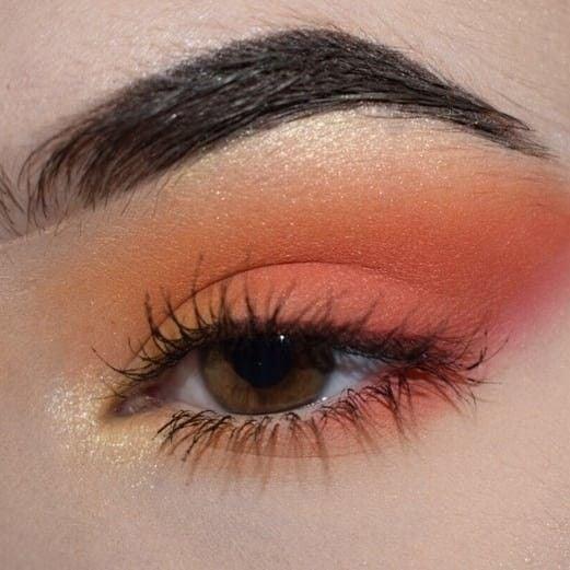 Maquillaje de ojos con sombras naranjas, rosas, amarillas y un toque de luz en el lagrimal