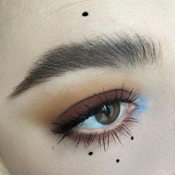 Maquillaje de ojos sencillo con ahumado tenue con sombra café en el párpado, sombra azul en el lagrimal y puntos de delineador