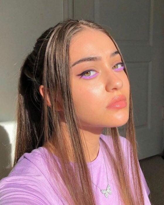 Chica de cabello castaño agarrado en una coleta con dos mechones sueltos, usa sombra morada en la parte inferior de los ojos