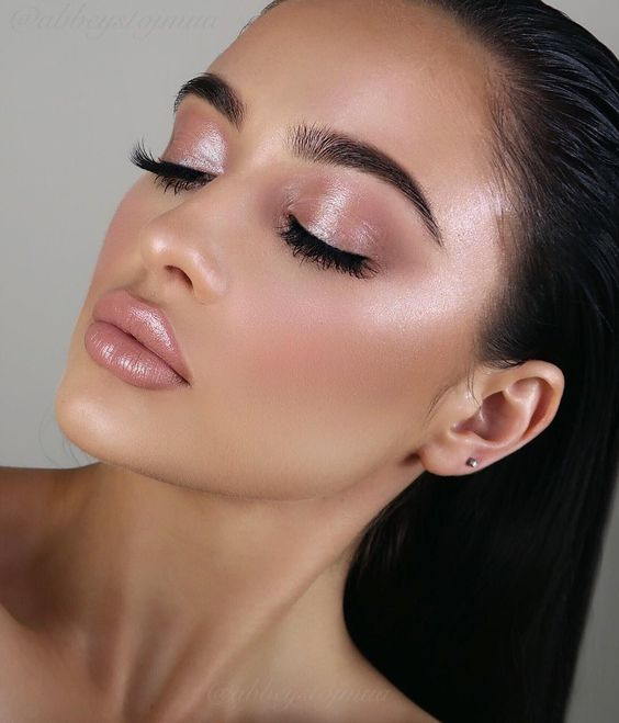 Mujer morena clara con coleta cierra los ojos y usa maquillaje natural en color rosita con un toque de brillo y un labial rosa con gloss