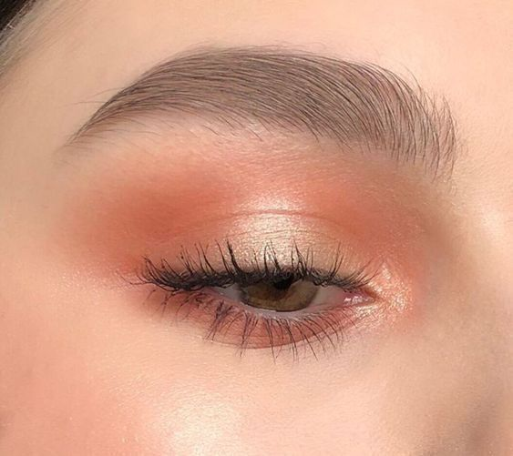 Coral eye makeup with pearl lids and soft brows