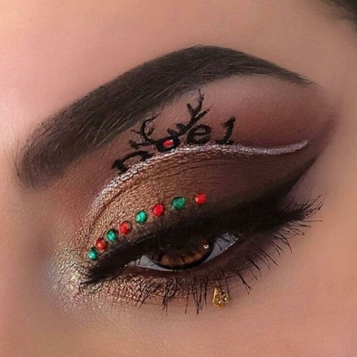 Chica con maquillaje de ojos en color café, delineado blanco y detalles en rojo;Maquillajes lindos para celebrar Navidad