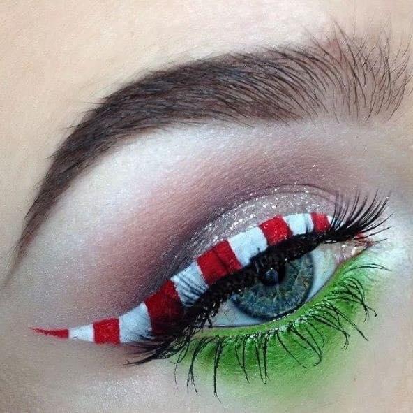 Chica con maquillaje de ojo delineado en color blanco, rojo y verde inspirado en El Grinch;Maquillajes lindos para celebrar Navidad