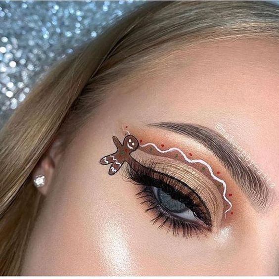 Girl with brown eye makeup, with a hanging gingerbread man; Cute makeup to celebrate Christmas