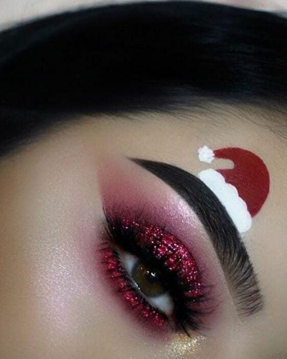 Chica con maquillaje para ojos en color rojo, con glitter; Maquillajes lindos para celebrar Navidad