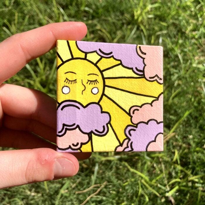 Minipintura en lienzo pequeño al óleo de sol con rostro y nubes rosas