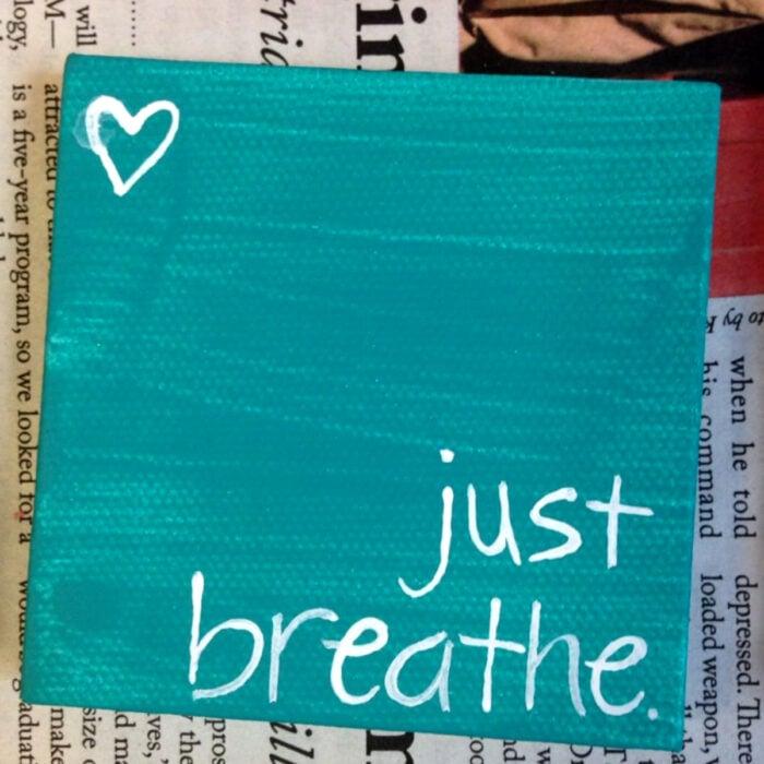 Minipintura en lienzo pequeño al óleo con frase 'just breathe' sobre fondo azul turquesa