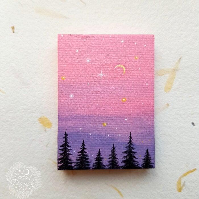 Minipintura en lienzo pequeño al óleo de paisaje de silueta de pinos con cielo estrellado color rosa y morado