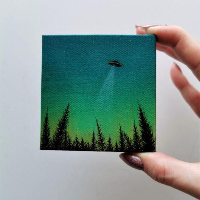 Minipintura en lienzo pequeño al óleo de paisaje de silueta de pinos, cielo verde y OVNI