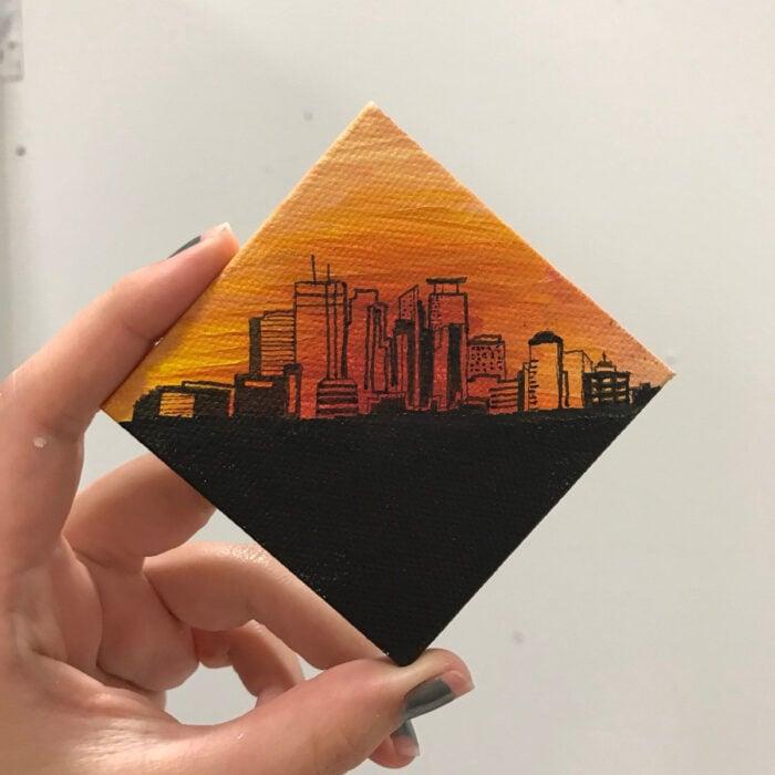Minipintura en lienzo pequeño al óleo de paisaje de ciudad con cielo anaranjado