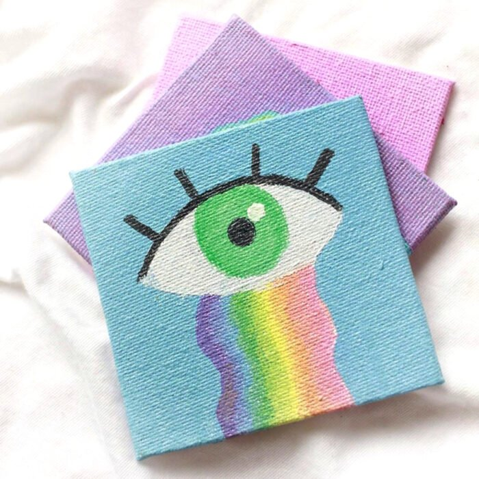 Minipintura en lienzo pequeño al óleo de ojo minimalista de iris verde con lágrimas de arcoíris sobre fondo azul pastel