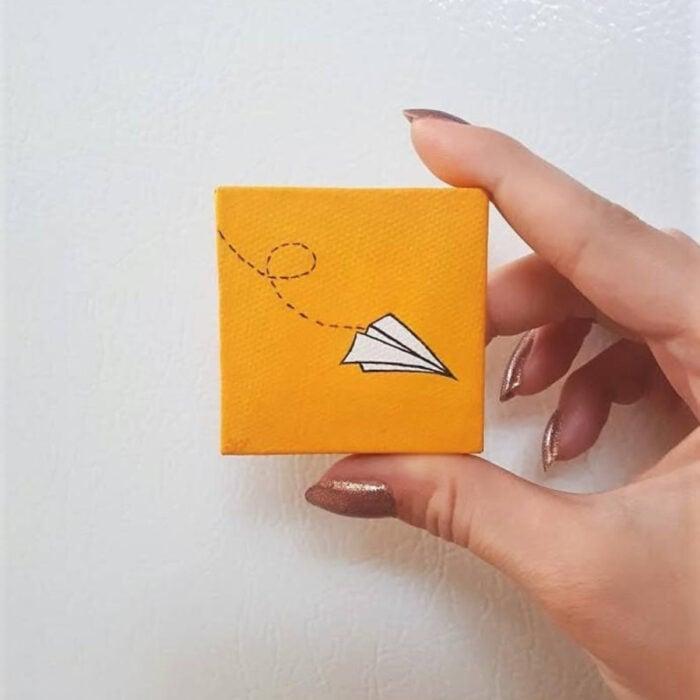 Minipintura en lienzo pequeño al óleo de avión de papel sobre fondo anaranjado